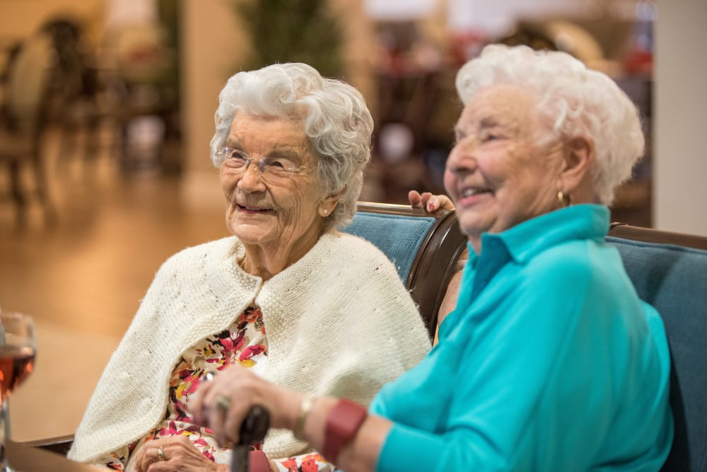 Two residents sitting on a couch at Inspired Living Ocoee in Ocoee, Florida.
