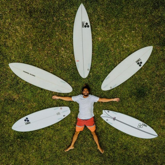 Man laying in grass surrounded by surf boards