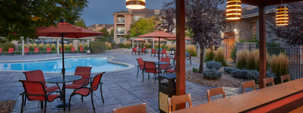 Poolside tables and chairs on a beautiful evening at Hawthorne Hill Apartments in Thornton, Colorado