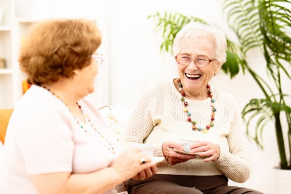 Two residents spending time with each other and laughing at White Springs Senior Living in Warrenton, Virginia