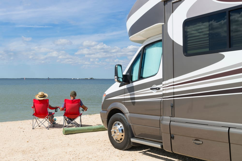 Couple sitting on a lakeside beach with their RV