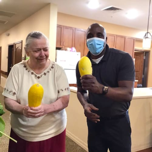 Team member with a resident holding gourds at Oxford Glen Memory Care at Grand Prairie in Grand Prairie, Texas