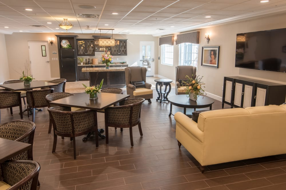 Dining room with a couch and TV at Inspired Living Bonita Springs in Bonita Springs, Florida.