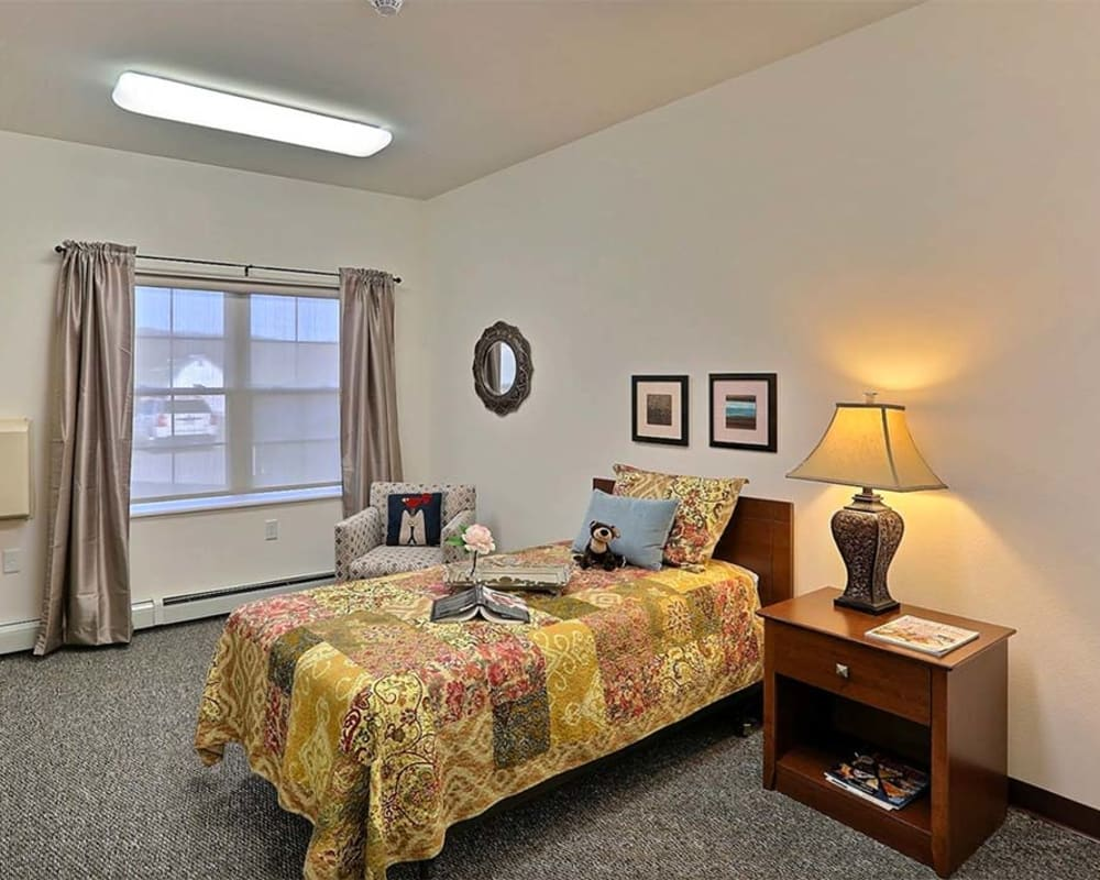Cozy bedroom with side table at Milestone Senior Living Cross Plains in Cross Plains, Wisconsin.