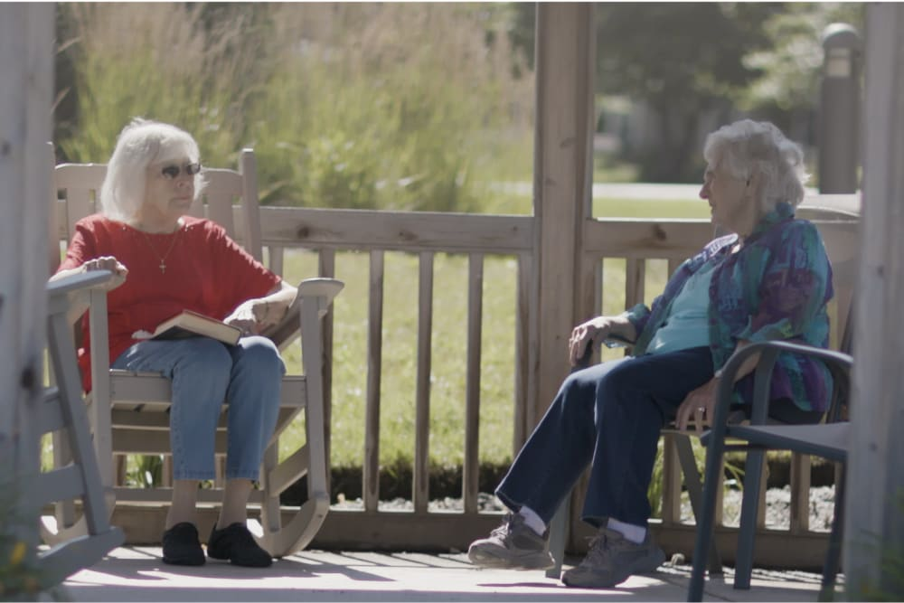 Two residents sitting outside on a sunny day at a Anthology Senior Living community