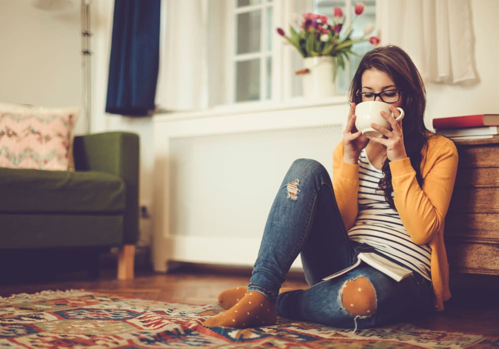 Resident relaxing with a cup of tea in her apartment home at Sofi Redwood Park in Redwood City, California