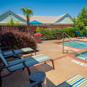 Lounging chairs outdoors on a sunny day next to a pool at Sunstone Village in Denton, Texas