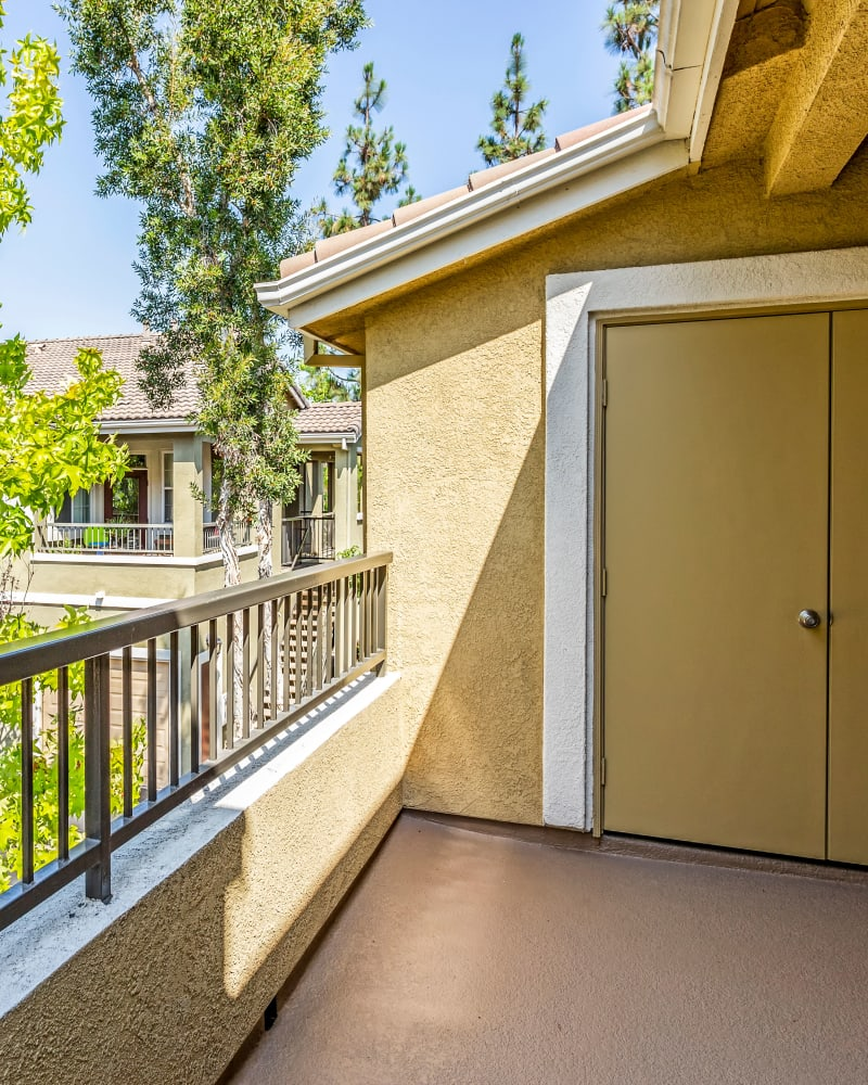 Private balcony with mature trees nearby for added privacy outside an apartment home at Sofi Highlands in San Diego, California