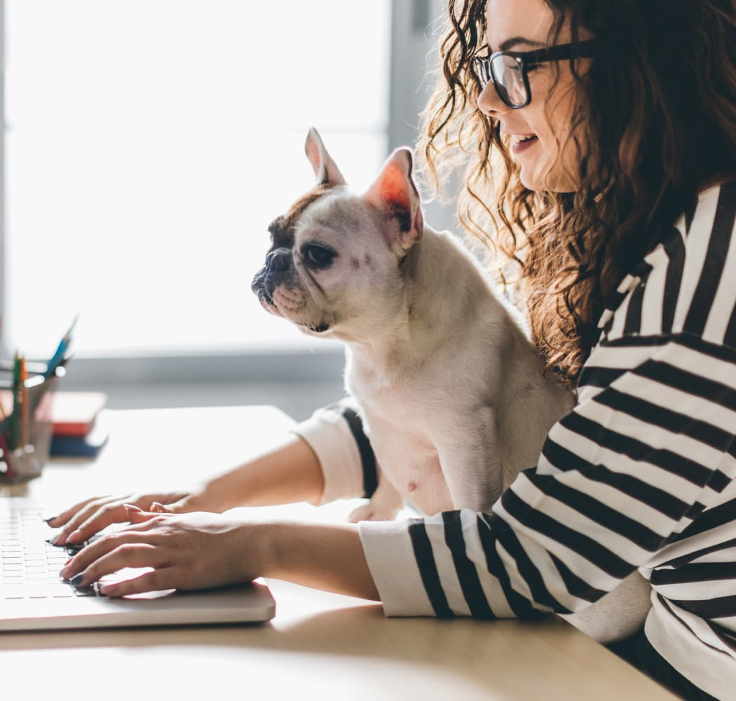 Resident working on her laptop with her dog at Eagle Point Apartments in Tulsa, Oklahoma