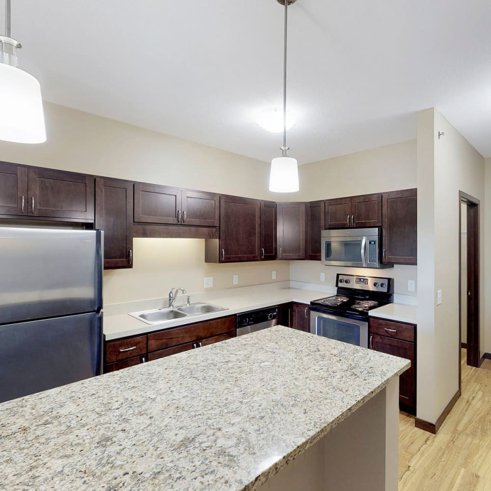 Granite countertops and stainless-steel appliances in a model home's kitchen at Oaks Station Place in Minneapolis, Minnesota