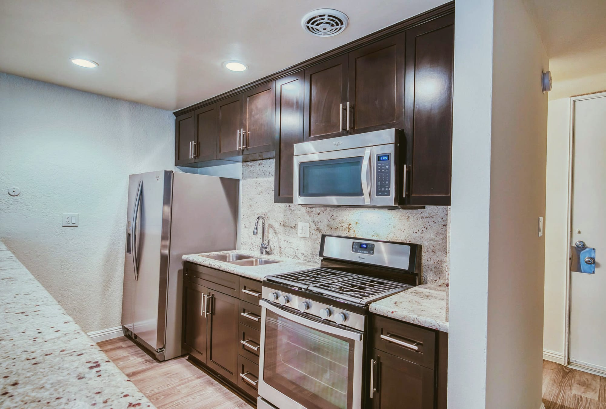 Model home's kitchen with espresso wood cabinetry and granite countertops at Mediterranean Village in West Hollywood, California