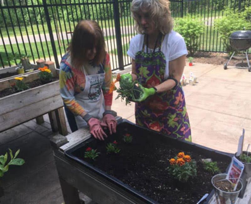 Residents planting flowers outside at Deephaven Woods in Deephaven, Minnesota