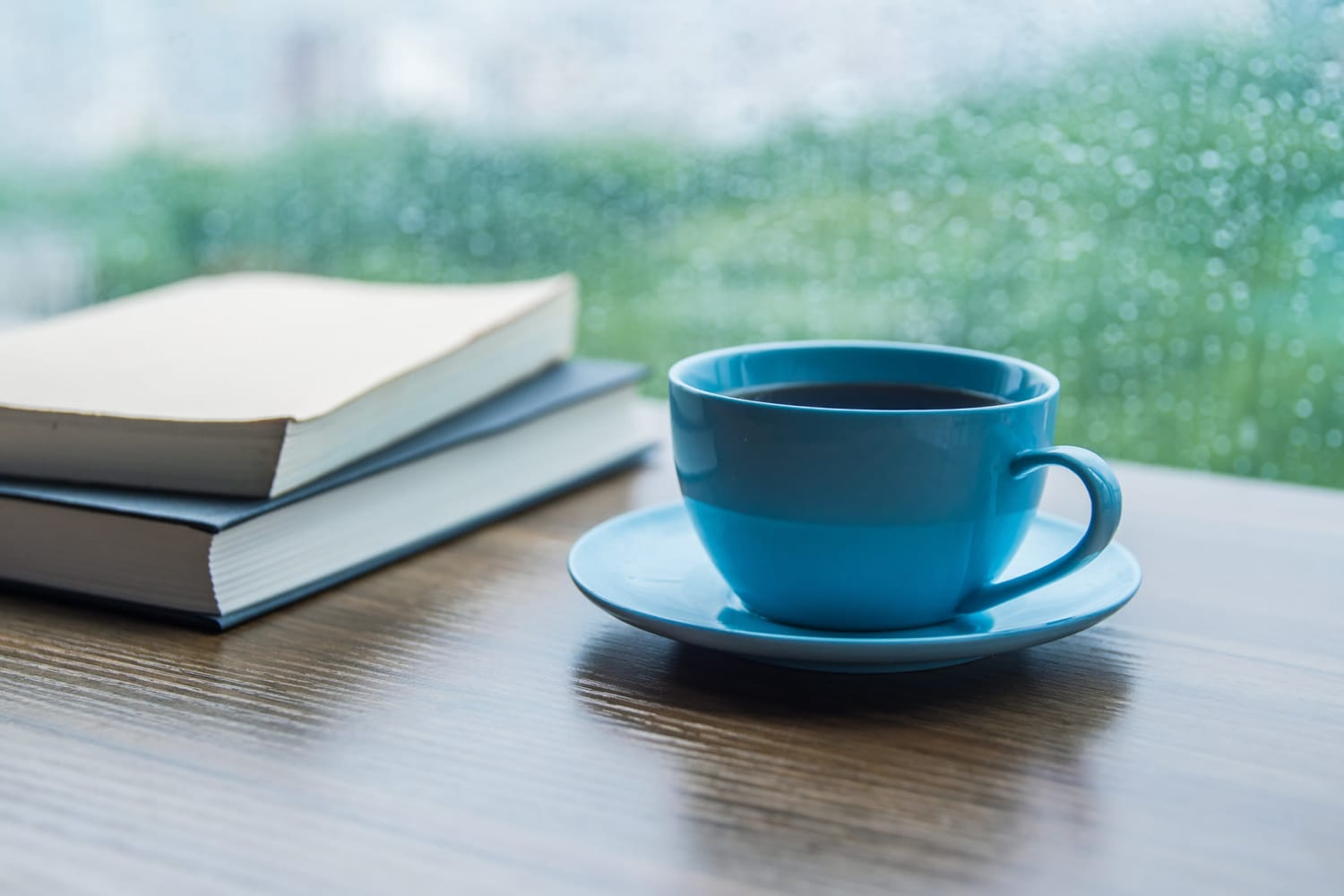 A cup of coffee and books on a table near a window at Farmington Square Tualatin in Tualatin, Oregon
