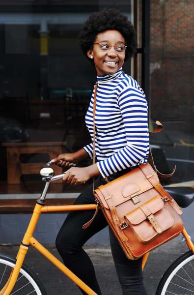 Woman walking her bike in Watertown, Massachusetts near Riverbend on the Charles