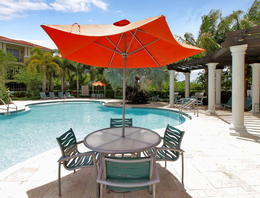 Shaded seating near the pool and pergola at IMT Miramar in Miramar, FL