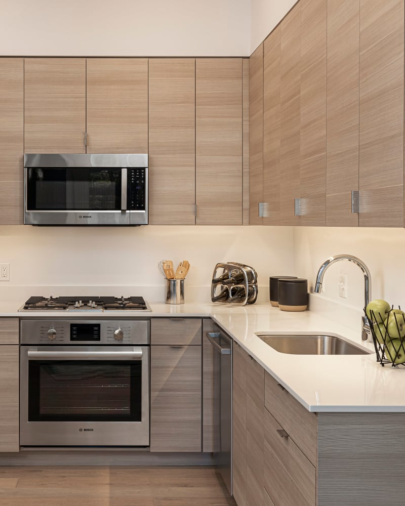 Gourmet kitchen with quartz countertops and stainless-steel appliances in a model home at TwentyTwenty Apartments in Portland, Oregon