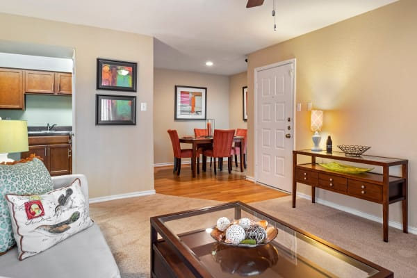Open living room and dining area with pass-through to the kitchen in a model apartment home at Foundations at Austin Colony in Sugar Land, Texas