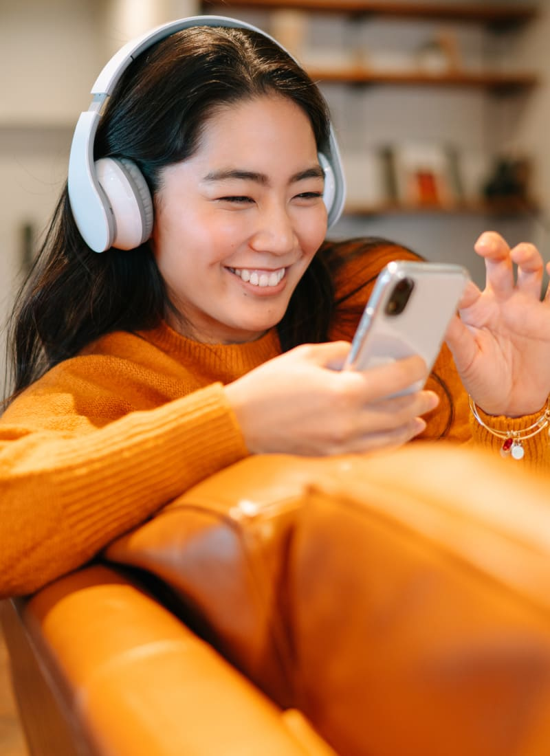 Resident listening to music on headphones while on smartphone at Marquis at Clear Lake in Webster, Texas