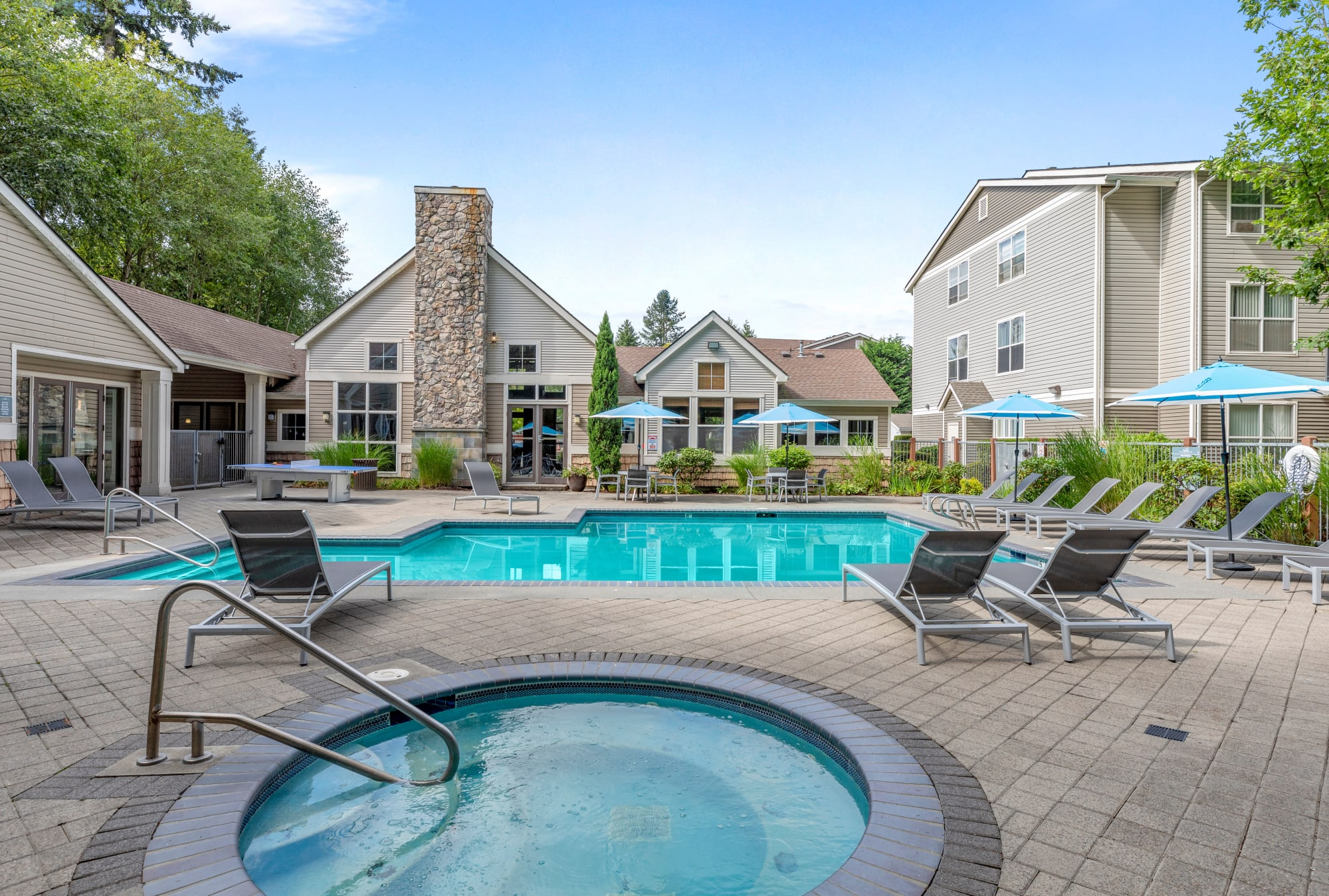 Pool view with Ping Pong Table and Lounge Chairs at Wildreed Apartments in Everett, WA
