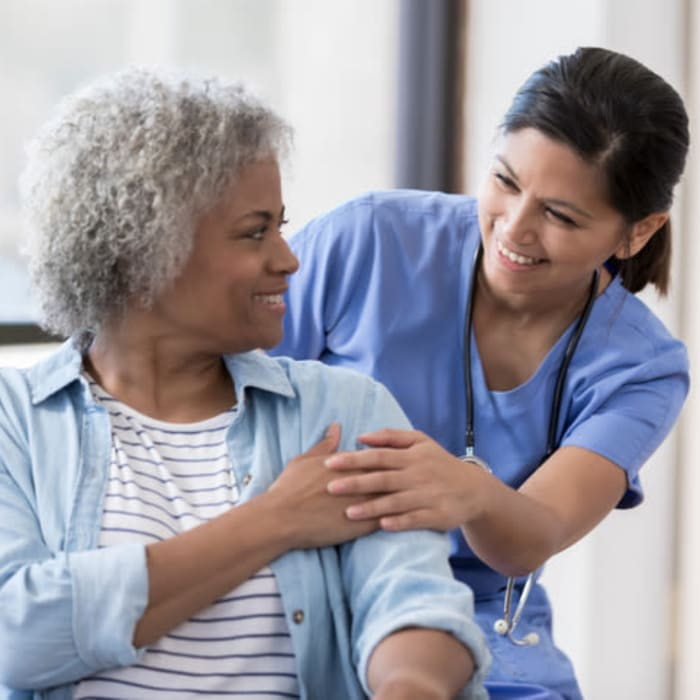 A nurse holding a resident's hand at Harmony Senior Services in Charleston, South Carolina
