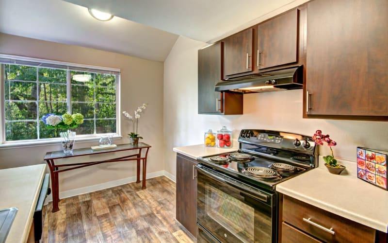 An updated kitchen with brown wood cabinets at Wellington Apartment Homes in Silverdale, Washington