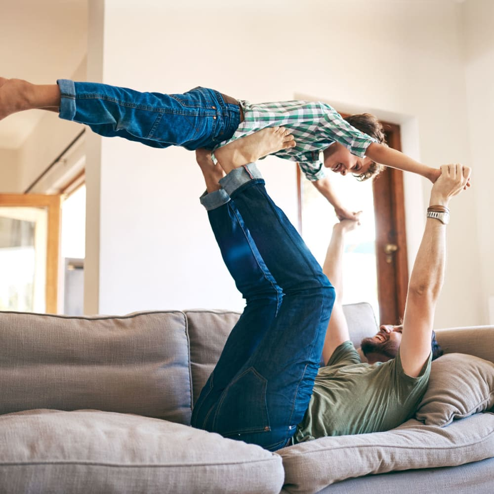 Father and son playing before school in the living area of their home at Oaks White Rock in Dallas, Texas