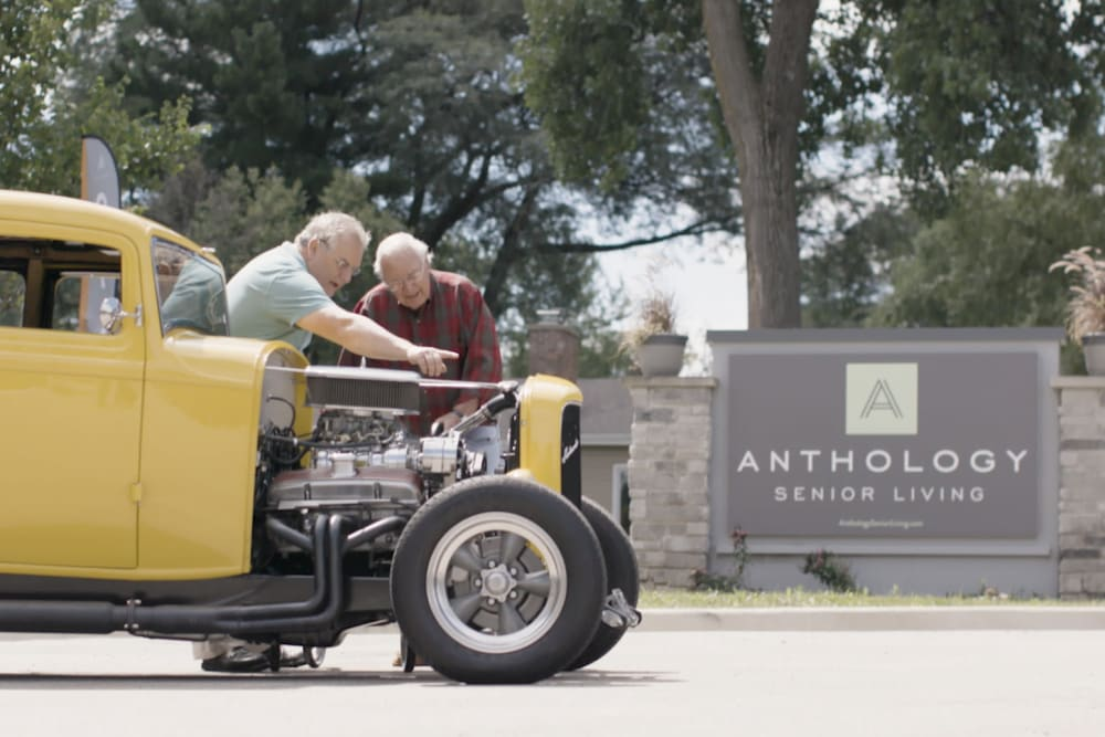 Two residents working on an old-school car at a Anthology Senior Living location
