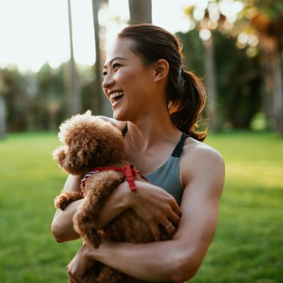 Resident holding her dog in a park near The Park at Flower Mound in Flower Mound, Texas
