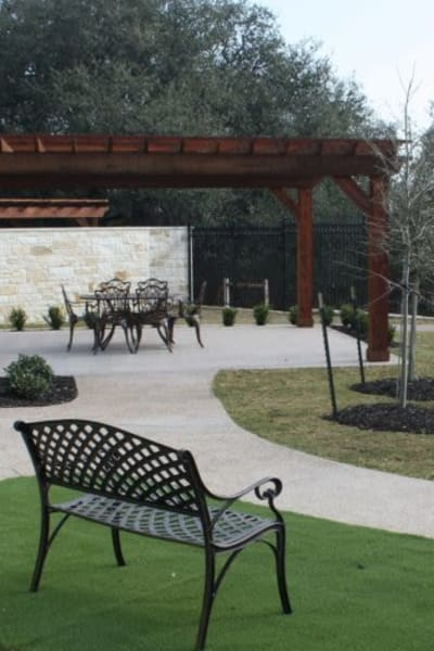 Courtyard with paved paths and benches at Quail Park of Granbury in Granbury, Texas