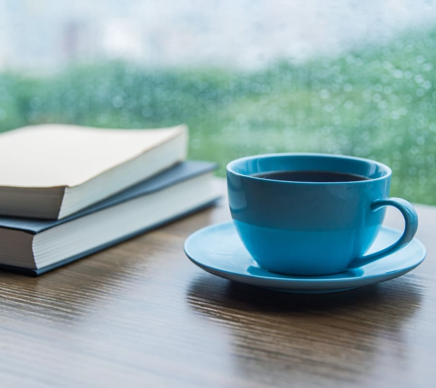 A cup of coffee and books on a table near a window at Bozeman Lodge in Bozeman, Montana