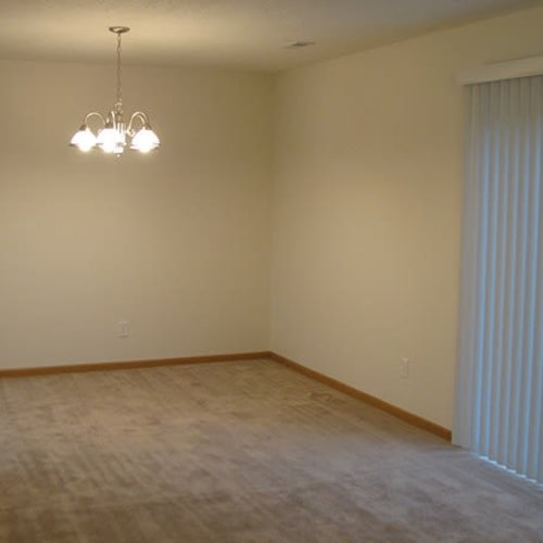 Spacious living area with plush carpeting at Indian Footprints Apartments in Harrison, Ohio