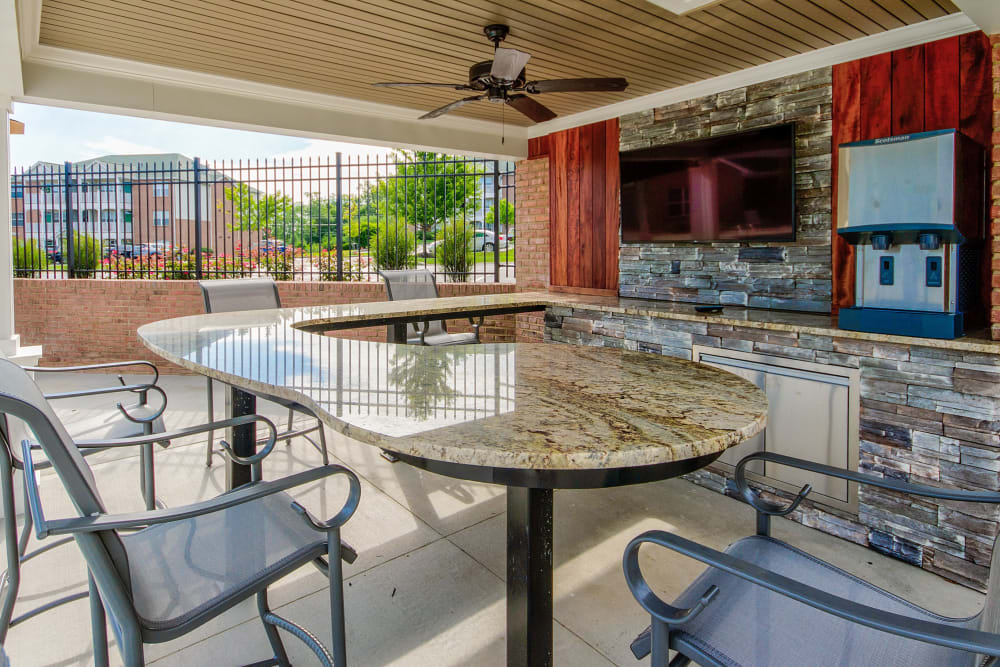 Table and chairs to sit in and watch tv in the covered area near the pool at Aspen Pines Apartment Homes in Wilder, Kentucky