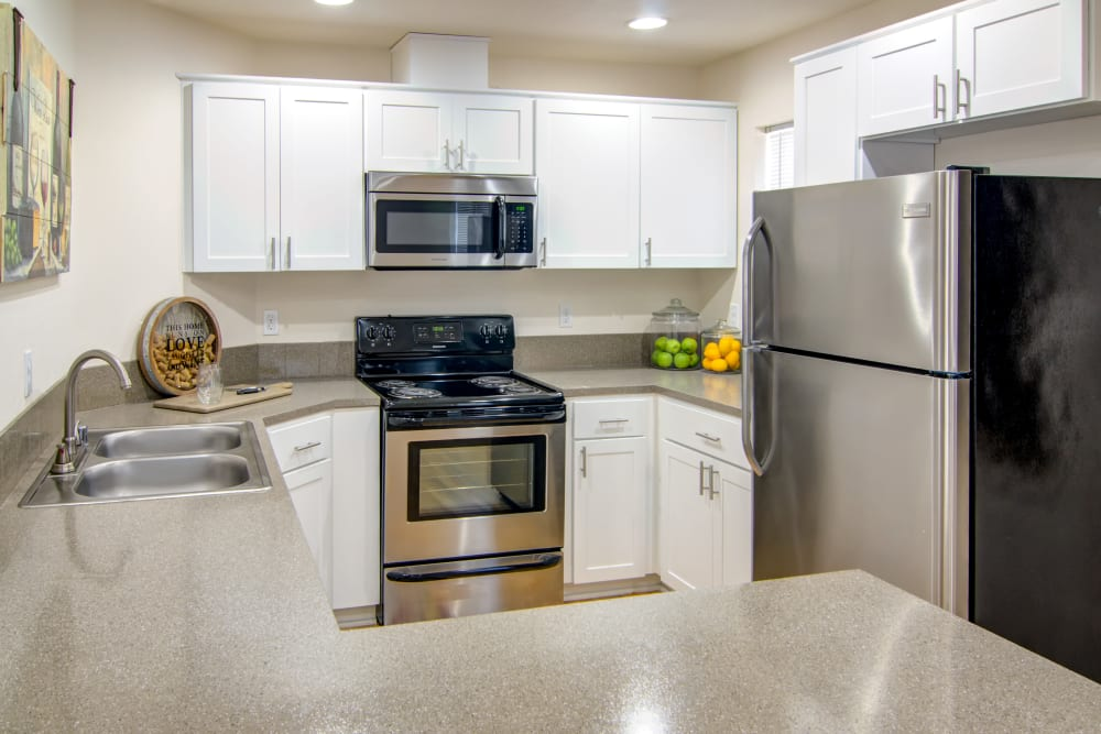 Kitchen with stainless steel appliances and white cabinetry at The Addison Apartments in Vancouver, Washington