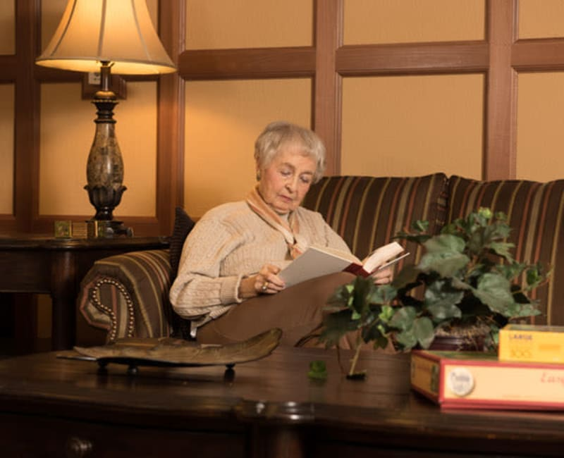 Resident sitting on a couch reading a book at York Gardens in Edina, Minnesota