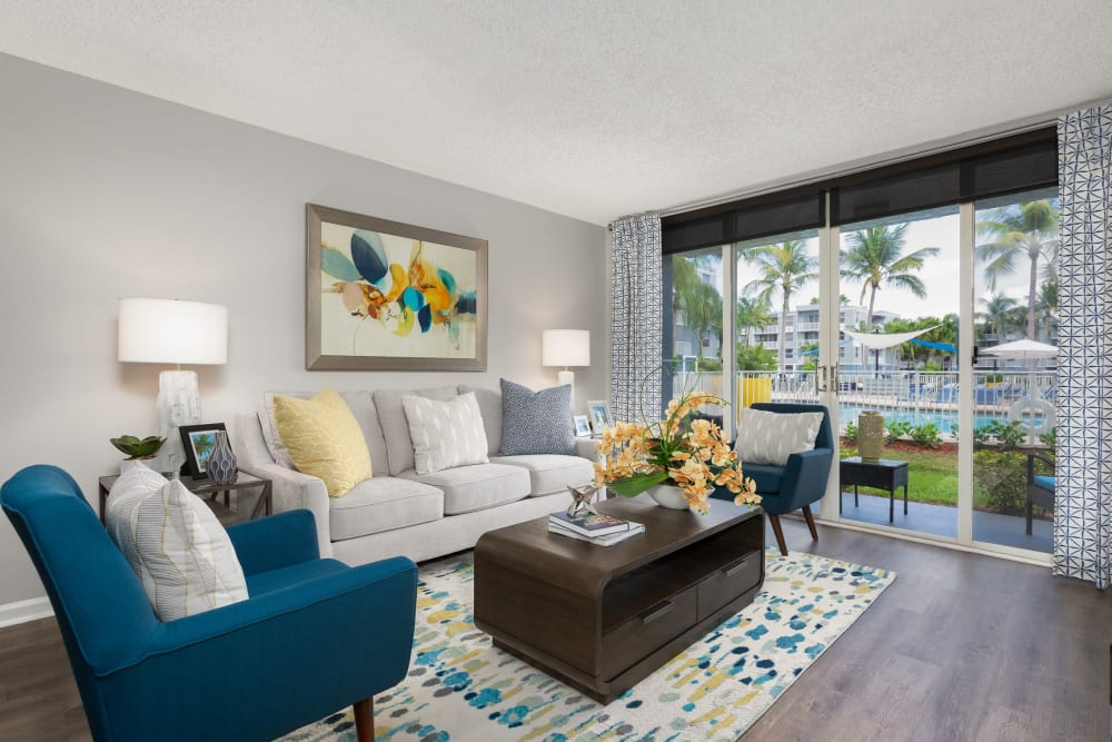 Living room area with wood style flooring and private patio access at Beach Walk at Sheridan in Dania Beach, Florida