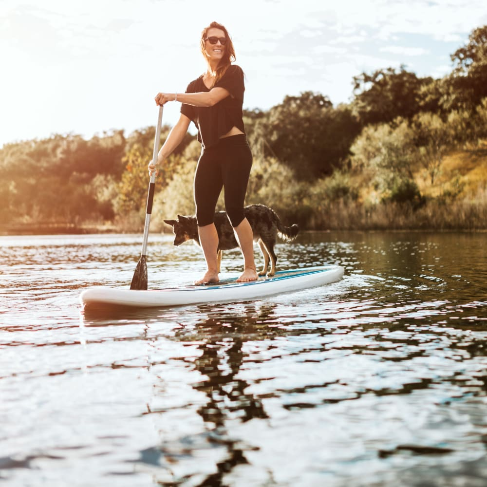 Resident stand-up paddleboarding near 4 Corners Apartments in Frisco, Texas