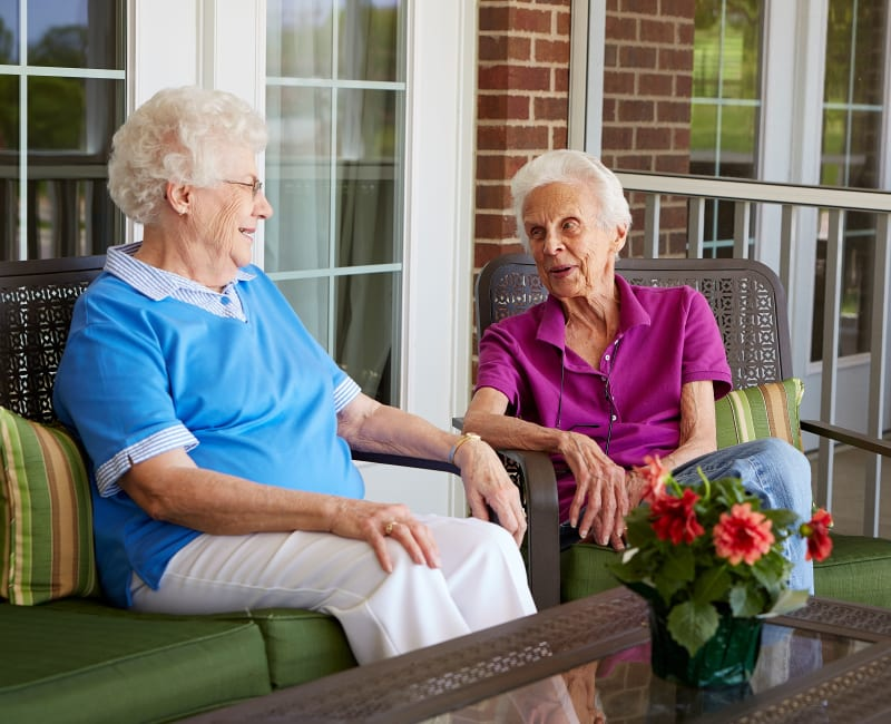Two residents sitting outside and talking at Deer Crest Senior Living in Red Wing, Minnesota