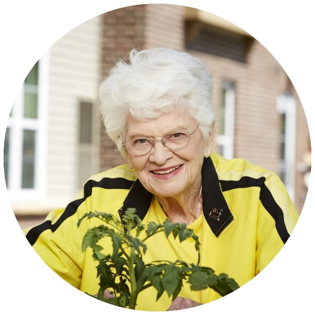 Resident planting flowers outside at Wildwood Manor Apartments