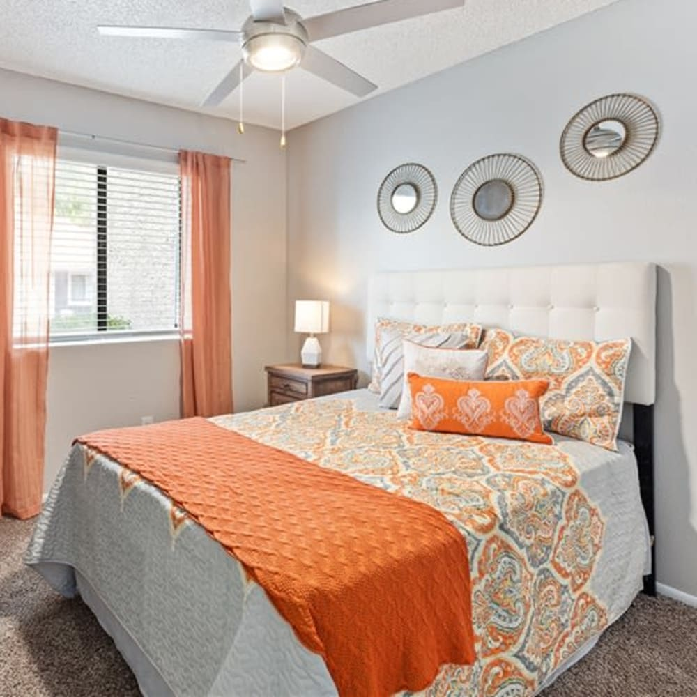 A bedroom with plush carpeting and a ceiling fan at Argenta Apartments in Mesa, Arizona