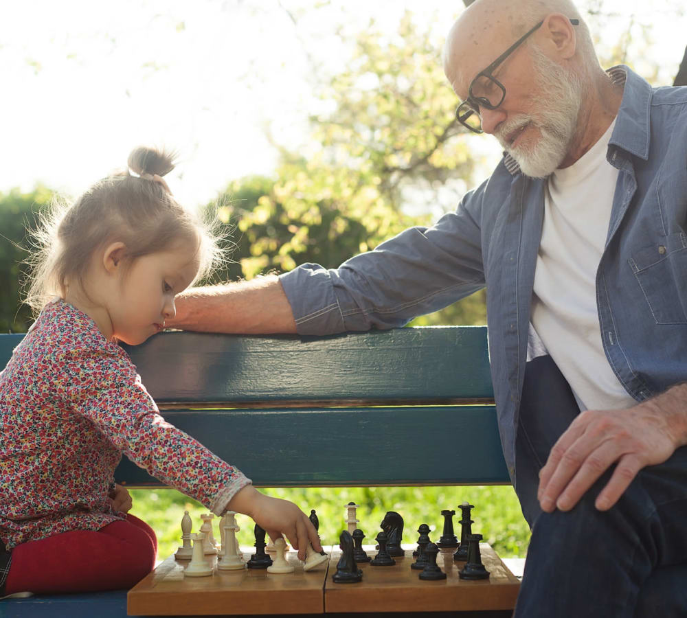 A resident from Touchmark at The Ranch in Prescott, Arizona playing chess with a child
