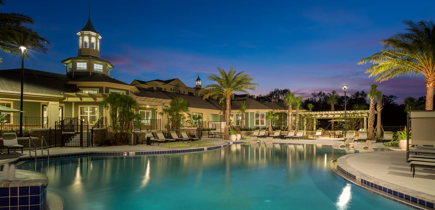 Nighttime view of swimming pool at Integra 360 Apartment Homes in Winter Springs, FL