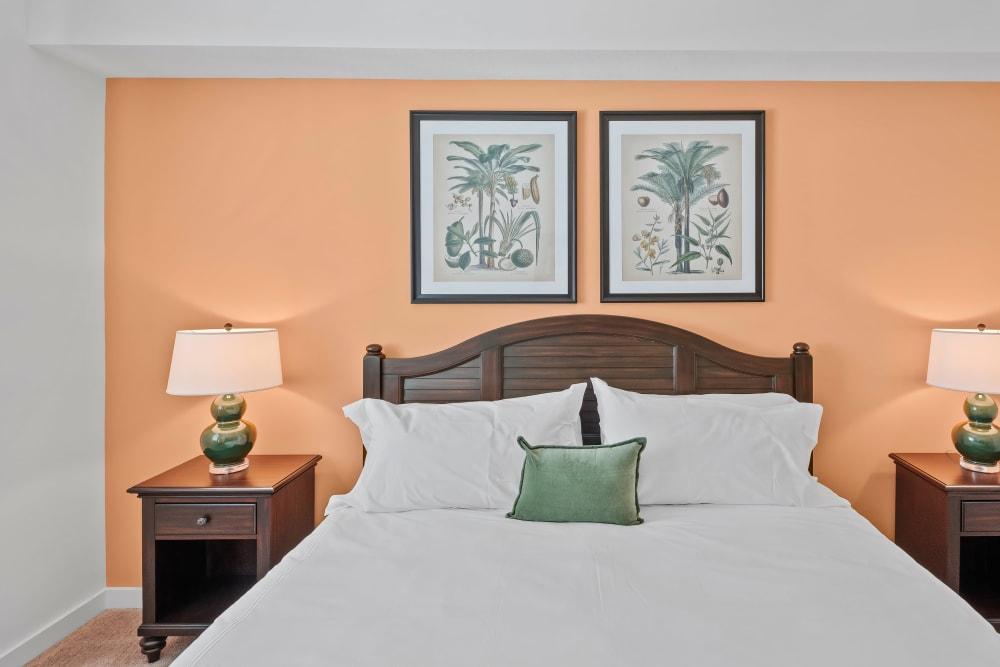 Model bedroom with light orange accent wall at Town Lantana in Lantana, Florida