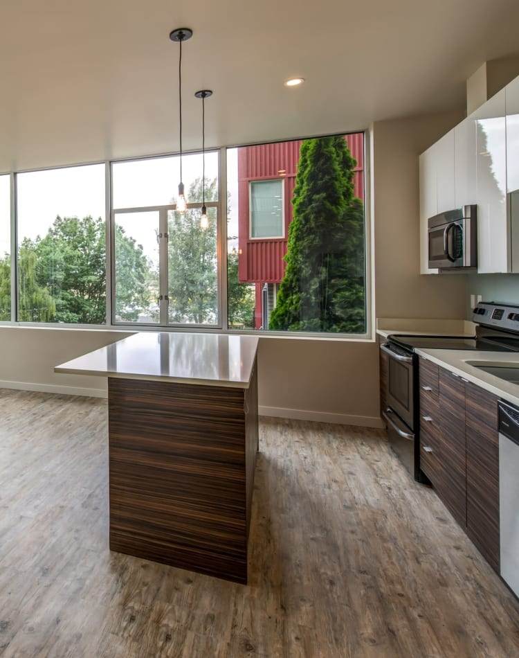 Modern kitchen with an island and stainless-steel appliances in the open-concept floor plan of a model home at Verse Seattle in Seattle, Washington