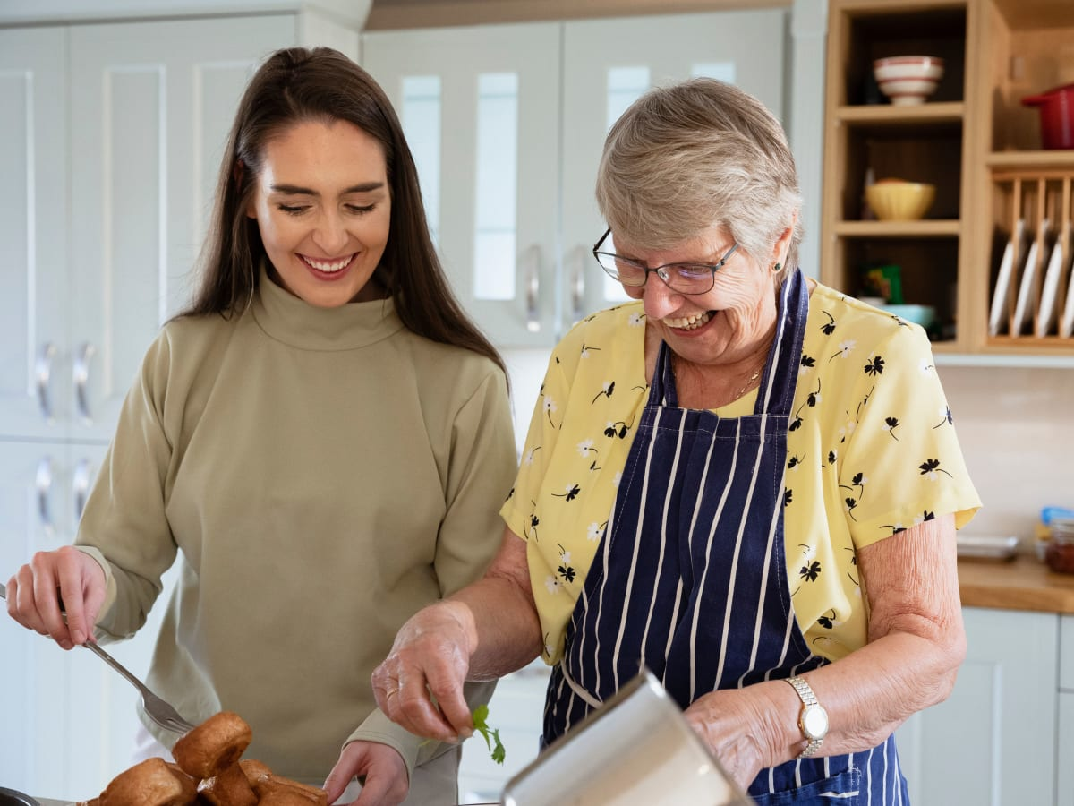 A resident and her daughter cooking at CERTUS Premier Memory Care Living in Vero Beach, Florida.