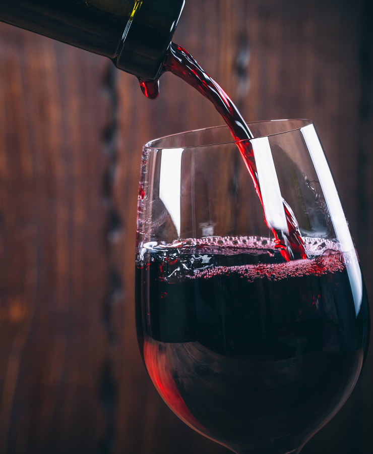 Close shot of a red wine being poured into a glass, near Collection 55 Cellars in Redwood City, California