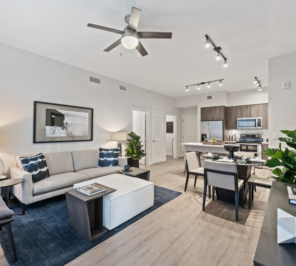 Light style modern decorated living area with wood floors and large windows at 6600 Main in Miami Lakes, Florida