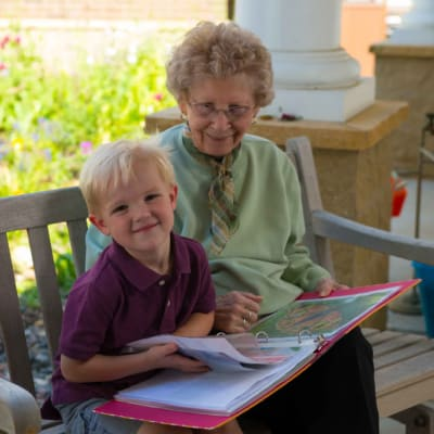 A resident reading a book with a child at Ebenezer Ridges Campus in Burnsville, Minnesota