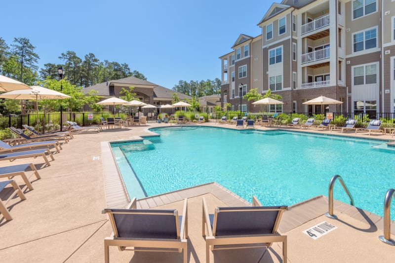 Resort-style swimming pool flanked by chaise lounge chairs and lush vegetation at Sterling Town Center in Raleigh, North Carolina