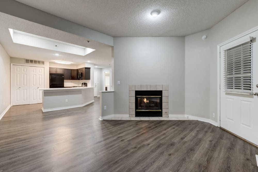 Spacious living room offering wood-style flooring and a wood burning fireplace at Ashford Belmar in Lakewood, Colorado