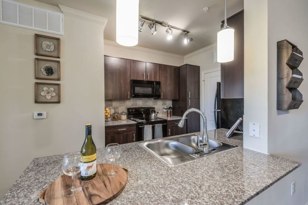 Model kitchen with granite countertops and ebony european-style cabinets at Heights West 11th in Houston, Texas